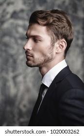 Portrait of an elegant young man over grunge background. Studio shot.
