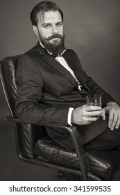 Portrait of an elegant young  man with retro look sitting in an armchair and holding a glass of whiskey over gray background