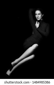 Portrait of elegant young woman in black elegant dress.Black and white.Long legs.