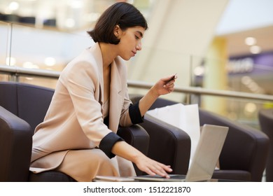 Portrait of elegant young woman holding credit card while using laptop enjoying e-shopping in mall, copy space