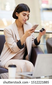 Portrait of elegant young woman holding credit card and smartphone while buying clothes online enjoying e-shopping