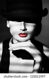 Portrait of the elegant young woman posing in black pot hat. Light and shadow.