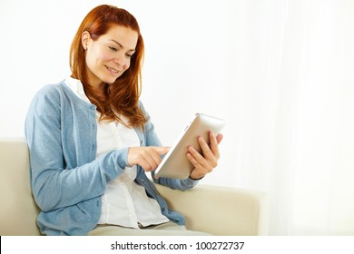 Portrait of a elegant young woman using a tablet PC while resting