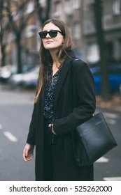 portrait of an elegant young woman wearing the perfect fall outfit. fashion blogger posing  in a black, oversized coat, combined with black high waist trousers and a v-neck see through shirt