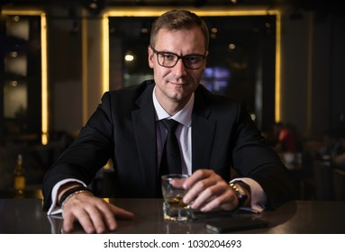 A portrait of an elegant,serious and cheerful businessman sitting in the holding a glass of whiskey and lookong at camera