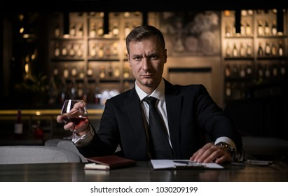 Portrait of an elegant,serious and concentrated businessman holding a glass of cognac and looking at camera