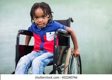 Portrait of elementary handicapped boy against board in classroom