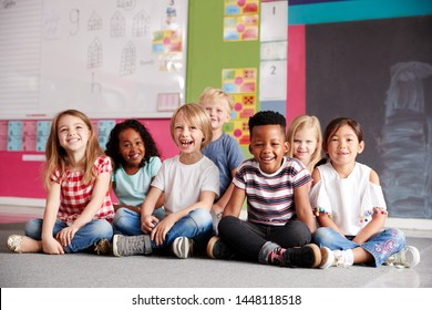 Portrait Of Elementary School Pupils Sitting On Floor In Classroom