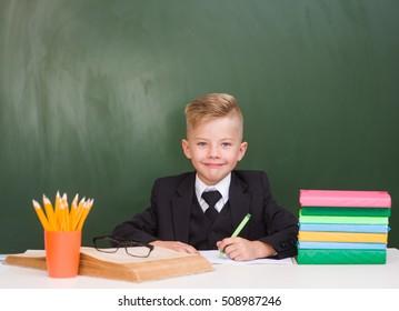 Portrait of elementary school student near empty green chalkboard
