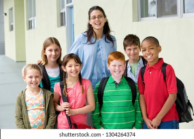 Portrait of elementary school teacher outdoors with students at camera