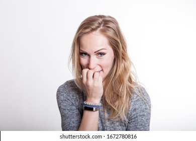 portrait of an embarassed blond woman chewing nails due to her nervousity