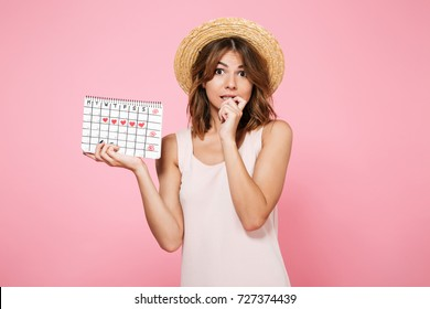 Portrait of embarrassed ?ute girl in summer hat holding calendar with drawn hearts and looking at camera isolated over pink background