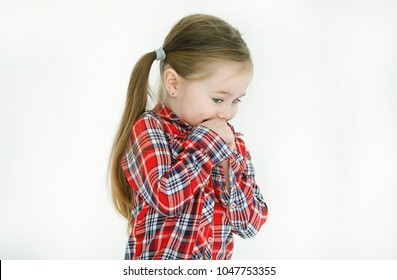 Portrait of an embarrassed and shy beautiful little girl in a checkered shirt looking modestly in the floor covering her mouth with her hands isolated against a white background in the studio