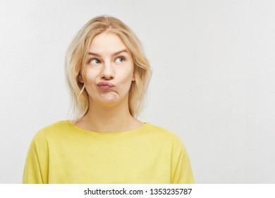 Portrait of an embarrassed young woman with a confused mouth in yellow clothes on a white background with free space for your text