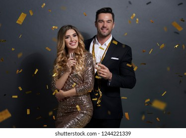 Portrait of embraced couple drinking alcohol at studio shot