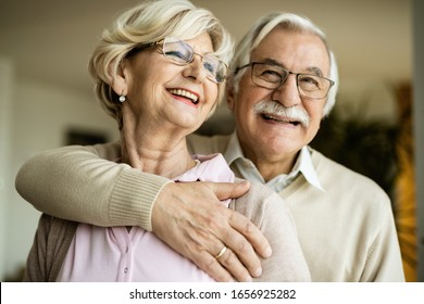 Portrait of embraced and happy senior couple at home.