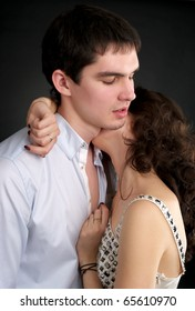 Portrait of embracing beautiful sexual couple over black