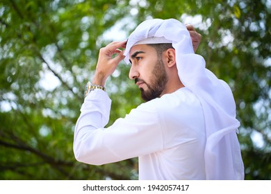 Portrait of Emirati Arab man on Kandura. Standing Arabic male model wearing traditional white clothing in the Middle East Gulf