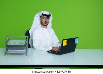 Portrait of Emirati businessman using laptop