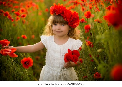 Portrait of emotional baby girl in red poppy field spring inspiration