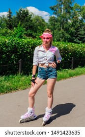 Portrait of an emotional beautiful young girl in a pink cap visor and protective gloves for rollerblades and skateboarding riding on rollerblades on the road.