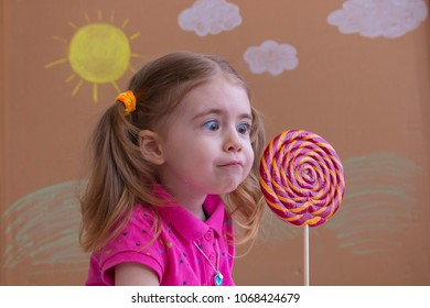 portrait of emotional girl with big sugar lollipop, kid eat sweets. background of painted sun and white clouds, studio.