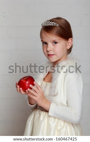 366e4e35db2 Portrait of emotional little girl holding a red apple on a gray  background Smiling child in a white dress with a tiara holding an apple -  Image