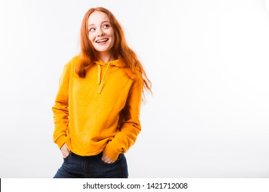 Portrait of an emotional red-haired girl with freckles and braces on a white background.