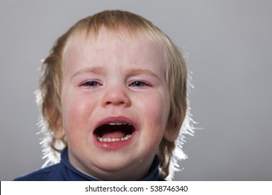 portrait of emotional tears crying baby toddler blond long hair