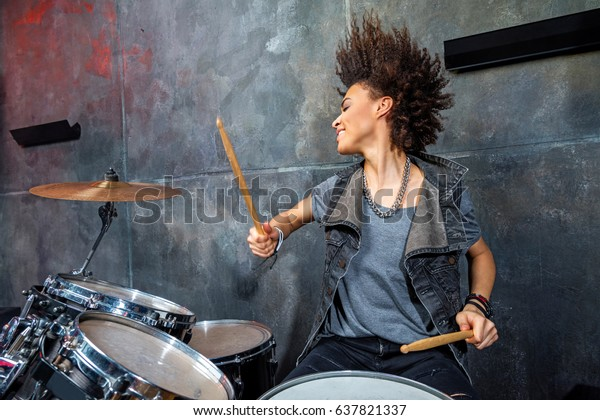 portrait of emotional woman playing drums in studio, drummer rock concept
