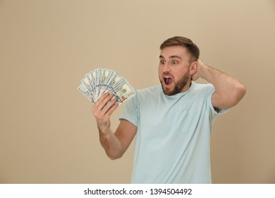 Portrait of emotional young man with money on color background