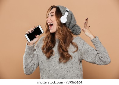 Portrait of emotional young woman in gray woolen hat holding her smartphone like microphone and singing, isolated on beige background