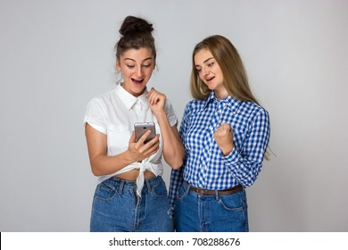 Portrait of a emotions, expressions, success and people concept - two sad young sisters or teenage girl celebrating victory  standing over gray background