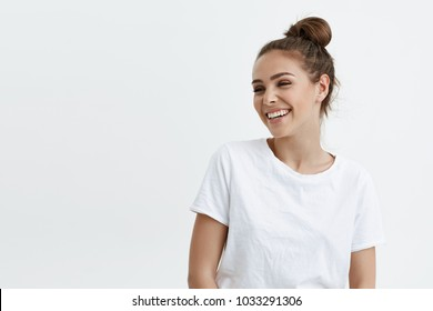 Portrait of emotive good-looking caucasian woman laughing while looking aside and standing against white background. Positive housewife on shopping with kids. Fashionable girl talks with friends