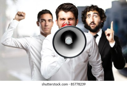 portrait of employees group shouting using a megaphone against a city background
