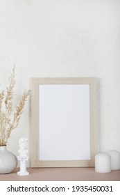 Portrait empty wooden frame mockup, dried pampas grass, small statue and candles on white background, interior, home design. Art concept. copy space.