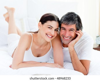 Portrait of an enamored couple embracing lying on their bed