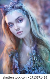 Portrait of an enchanting forest nymph with blue eyes and blonde hair covered with ice. Fairytale character.