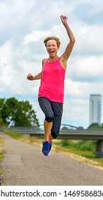 Portrait of a energetic motivated exuberant middle-aged woman running along a quiet rural road