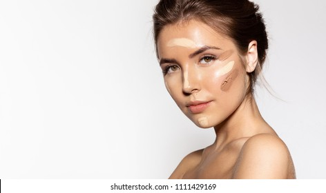 Portrait of engaging young woman with cosmetic tonal foundation on her face. Glorious brunette looking at camera with calmness. Beauty treatment concept
