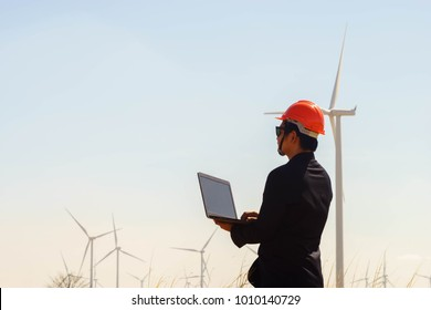Portrait of engineer asian man holding tablet with the wind turbine in background.