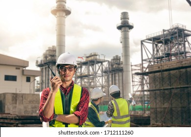 Portrait engineer construction working with team in cogeneration electrical plant. Asian man engineer contractor wearing safety helmet with Radio communication for working.