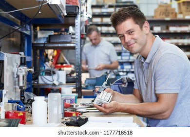 Portrait Of Engineer In Factory Measuring Component At Work Bench Using Micrometer