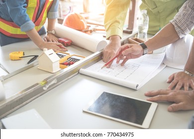 portrait engineer people working and discussing with blueprint and holding pencil on hand at construction site, using as background (concept of teamwork and partnership)