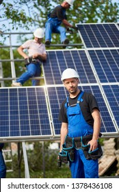 Portrait of engineer technician with electrical screwdriver standing in front of unfinished high exterior solar panel photo voltaic system blue shiny surface with team of workers on high platform.