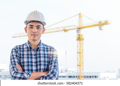 Portrait of engineer wear white safety helmet on construction site with crane background