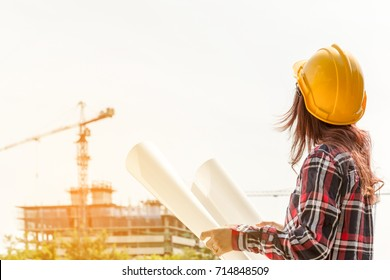 A portrait of engineer woman looking construction. Asian woman architect with blueprint in hand and yellow helmet with select focus and use effect filter. Concept Engineer and business work.