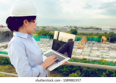 Portrait of engineer woman is using laptop inspection precast concrete product in factory.