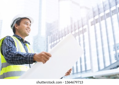 portrait of engineering asian man construction worker holding roll paper of drawing Structural plan safety white helmet and wear reflective clothing for the safety of the work operation.
