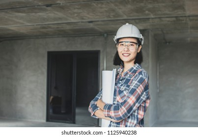 portrait of engineering women holding blueprint at construction site